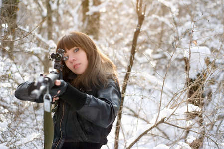 Girl aiming a gun in the forest photo