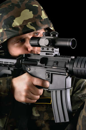 Armed soldier taking aim in studio. Closeup photo