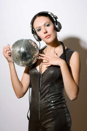 Portrait of sensual young brunette in headphones with a mirror ball photo