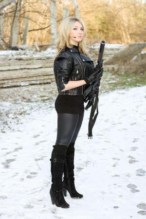 airsoft gun: Charming young woman with a gun outdoors