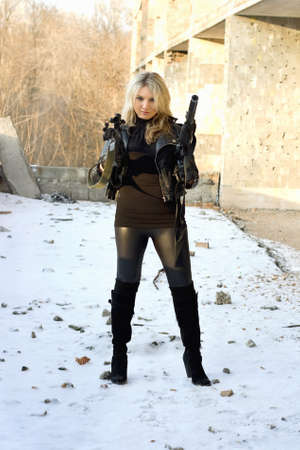 the silencer: Serious girl on the snow with rifle Stock Photo