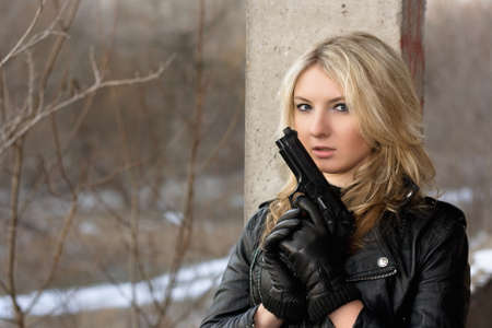 airsoft: Scared young woman in leather jacket with a gun Stock Photo