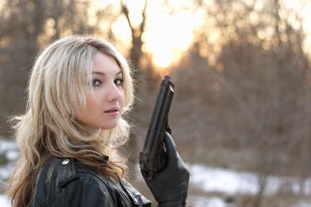 mujer con pistola: Mujer provocativa joven que sostiene un arma de fuego en el bosque de invierno
