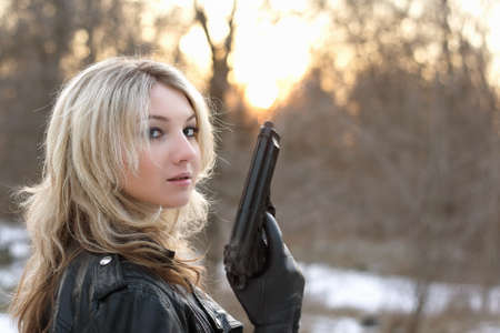 Provocative young woman holding a gun in winter forest