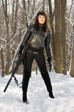 ljuddämparen: Vacker ung kvinna med ett gevär i skogen
