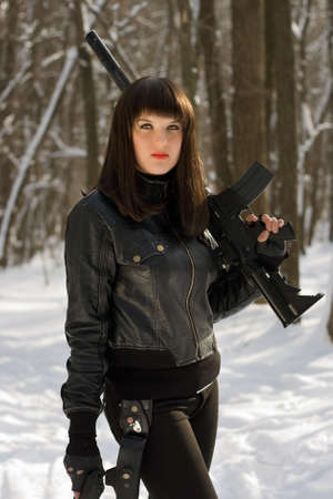 Portrait of beautiful young woman with a rifle in forest photo