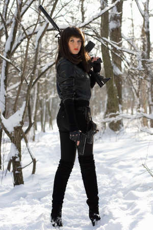 Armed sexy young woman in winter forest photo