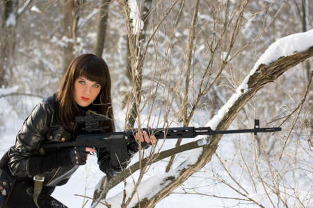 Portrait of pretty young woman with a sniper rifle in winter forest photo