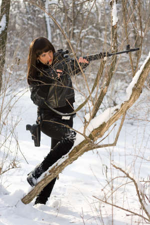 Sexy young woman with a sniper rifle in winter forest photo