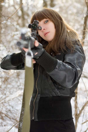 Brunette aiming a gun in the forest photo