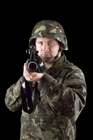 Armed man pointing a rifle in studio Stock Photo - 13413221
