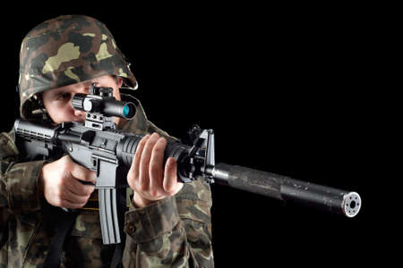 Armed man taking aim in studio. Closeup photo