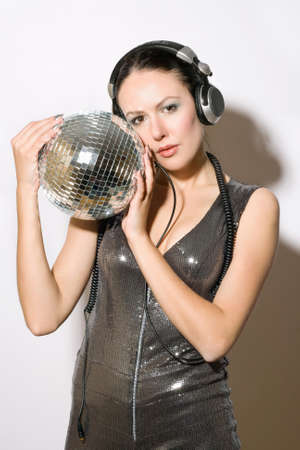 Portrait of beautiful young woman in headphones with a mirror ball photo