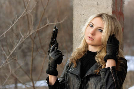 Confused blonde girl with weapon in her hands photo