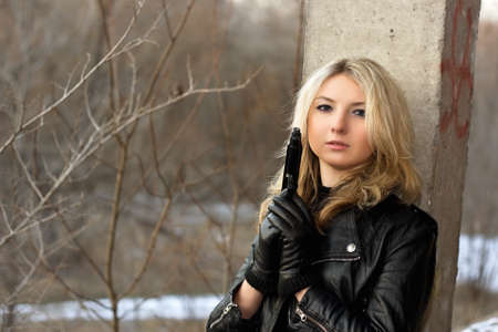 airsoft gun: Sensual young woman holding a weapon in front of the winter forest