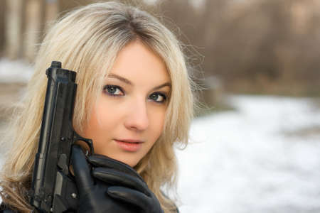 killer: Sweet woman with a weapon in winter forest
