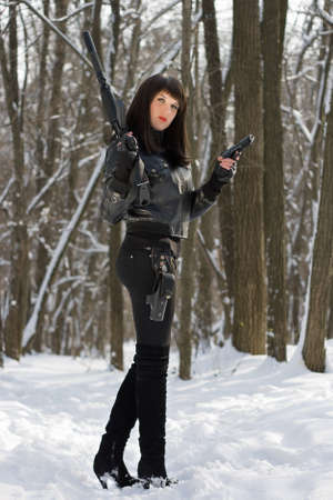 Gorgeous young woman with a rifle in forest photo