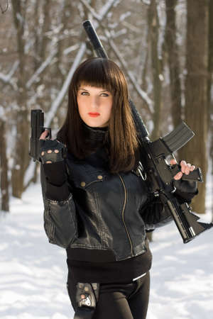 Portrait of attractive young woman with weapon in their hands photo