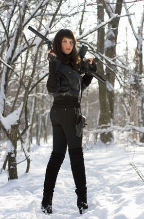 Armed attractive young woman in winter forest photo