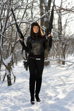 Armed pretty young woman in winter forest photo