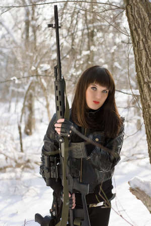 Portrait of beautiful young lady with a sniper rifle  photo
