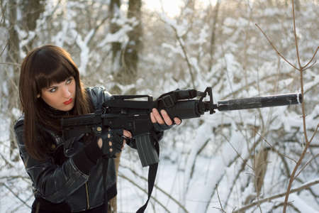 the silencer: Portrait of attractive young lady with a rifle