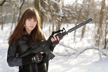 Beautiful armed girl in the winter forest Фото со стока