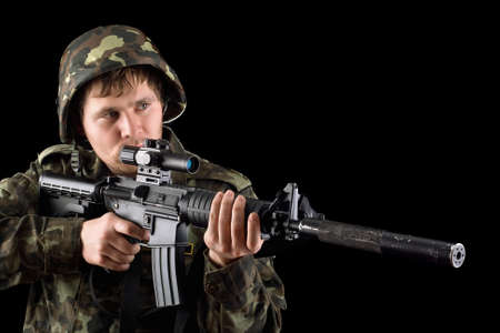 Aiming soldier with a rifle in studio. Isolated photo