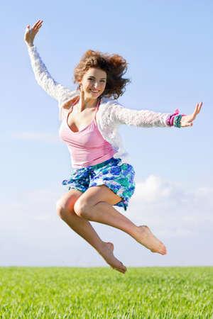 Joyful beautiful young woman in a green field Stock Photo
