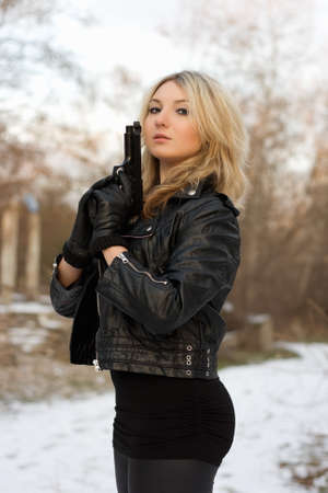 Arrogant pretty woman with a gun in winter forest photo