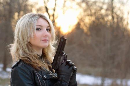 mujer con pistola: Provocador mujer joven en la puesta del sol en bosque de invierno