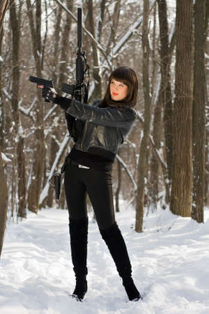 Attractive young woman with weapon in their hands photo