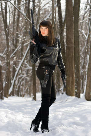 silencer: Strong young woman with a rifle in forest
