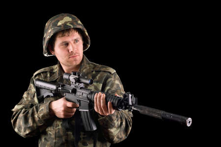 Arming soldier and a rifle in studio. Isolated photo