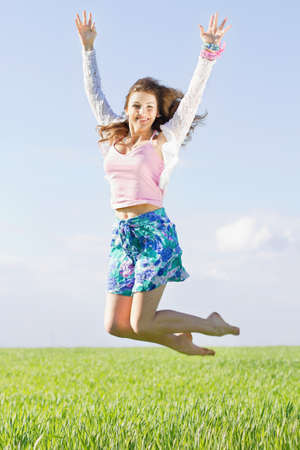 Cheerful beautiful young woman in a green field photo