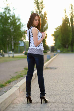Perfect young woman standing on the sidewalk photo