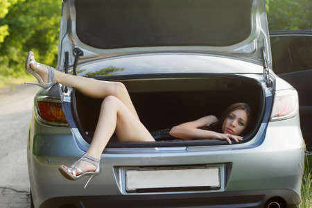Sexy young woman in the trunk of car
