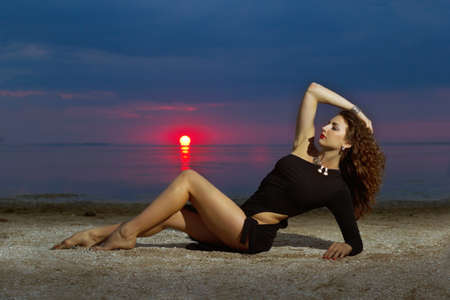 Attractive young woman lying on the shore at sunset photo