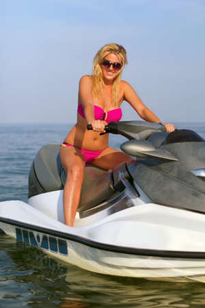 Sexy smiling young woman on a jet ski photo