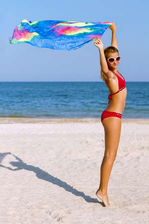 Cute teen girl standing on the beach with pareo in hands photo