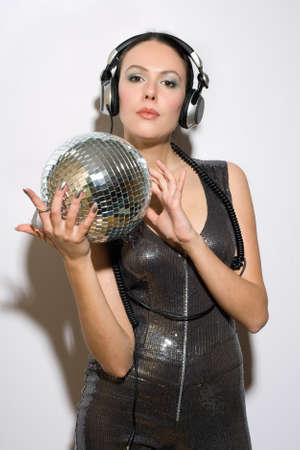 Portrait of beautiful young brunette in headphones with a mirror ball photo