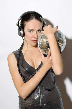 Portrait of sensual young woman in headphones with a mirror ball photo