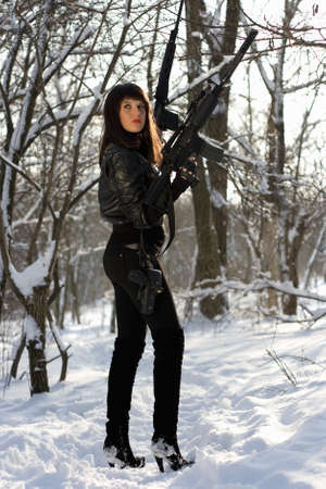 Armed pretty young lady in winter forest photo