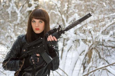 ljuddämparen: Porträtt av ung kvinna med ett gevär i vinter skog