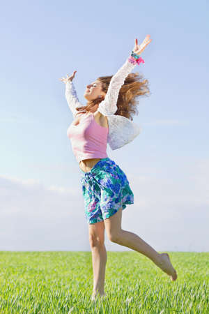 Happy beautiful young woman in a green field photo