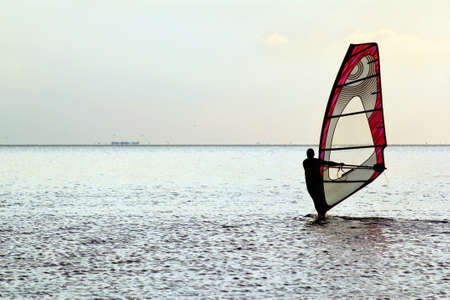 Man windsurfer on the water surface