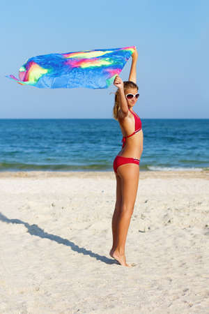 Beautiful teen girl standing on the beach with pareo in hands photo
