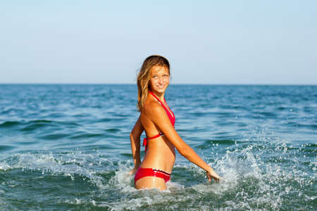 Happy teen girl having fun in the sea photo