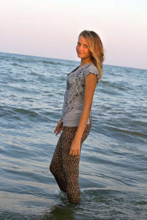 Dressed cute teen girl walks into the sea Stock Photo - 15688070