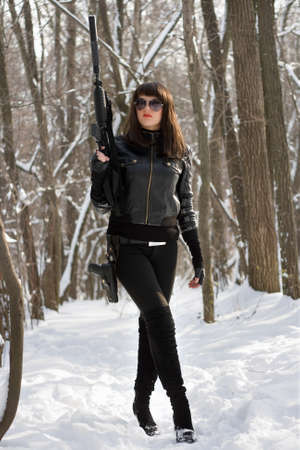 Beautiful girl with rifle among in forest photo